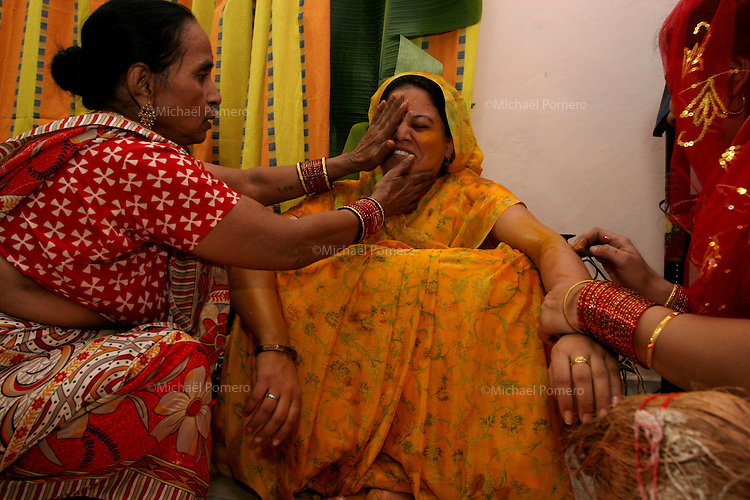 06.12.2008 Delhi(Haryana)<br /> <br /> Women of the family putting yellow oil on the body of the bride.<br /> <br /> Femmes de la famille de la mariée mettant de l'huile jaune sur le corps de la mariée;