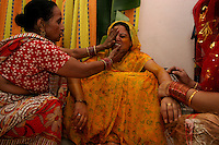 06.12.2008 Delhi(Haryana)<br /> <br /> Women of the family putting yellow oil on the body of the bride.<br /> <br /> Femmes de la famille de la mari&eacute;e mettant de l'huile jaune sur le corps de la mari&eacute;e;
