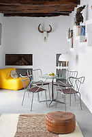 Metal chairs and a glass-topped table furnish this white-painted room with a rustic beamed ceiling