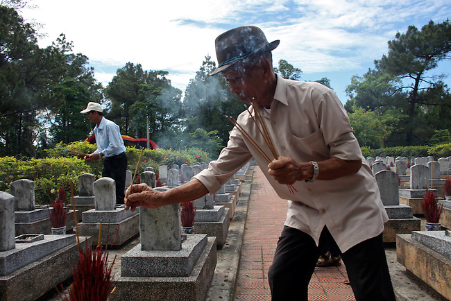 A Vietnamese war veteran places burning incense on the graves of fallen comrades at Truong Son Martyrs Cemetery in Quang Tri province, Vietnam. The cemetery contains the graves of about 10,300 communist soldiers who died along the Ho Chi Minh Trail supply network into South Vietnam during the conflict from 1959 to 1975. April 24, 2013.