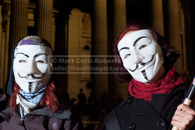 28/02/2012. LONDON, UK. Two protesters wearing Guy Fawkes masks stand outside a cordon as police and bailiffs remove the Occupy London campsite in London today (28/02/21). After being camped outside St Paul's Cathedral in London for four months anti-capitalist Occupy London demonstrators were tonight evicted by police and bailiffs who moved in shortly after midnight. Photo credit: Matt Cetti-Roberts