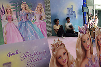 Two migrants lean against a billboard featuring the Barbie Dolls in Beijing, China..16-JUL-04