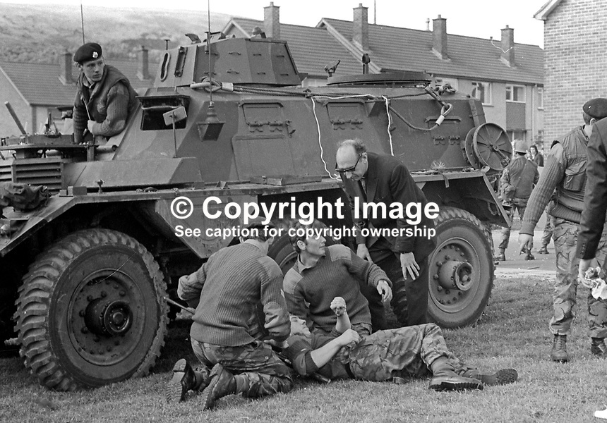 Soldier injured during rioting in the Roman Catholic Lenadoon public housing estate in West Belfast, N Ireland, is tended by colleagues, 9th July 1972. The disturbances occured after it was claimed that Roman Catholics tried to take over public housing in a nearby Protestant estate. 197207090379w<br />