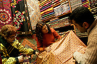 CUSTOMERS BUYING TEXTILES AT THE GRAND BAZAAR, ISTANBUL, TURKEY