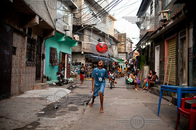 A boy plays with a ball in Complexo da Mare. The favela consists of a complex of 16 communities, in the north zone of Rio de Janeiro. It is the largest complex of favelas, housing 130,000 residents. It is targeted for pacification as the city prepares for the 2014 World Cup and the 2016 Olympics. Four factions run the complex, three drug gangs and the militia. The rival gangs fight for control of the drug trade. Although crime is low in the favelas by rule of law enforced by the gangs, cross-fire shootings and gang violence is often high. Neighborhood associations are an integral part of community development within Mare, making up for a lack of government assistance.