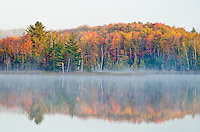 Morning light shows the mist rising off the waters of Council Lake in Autumn in the Hiawatha National Forest in Alger County, Michigan