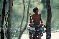 "Acculturated indian wearing shorts fishes at flooded forest of Uatumã river in a canoe using a ""zagaia"" (a typical kind of lance or spear) in Amazon rain forest ( State: Amazonas, Brazil )."