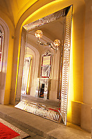 The entrance with mirror in crystal giants' arms holding candelabra reflections of a hand and a crystal fireplace, the red carpet with built in fibre optic lighting. At The Baccarat museum, shop, restaurant at the Hotel de Noailles in Paris. Designed by Philippe Starck. The Baccarat Museum entrance: A crystal mirror with a crystal arm holding a crystal light and a reflection of a crystal fire place