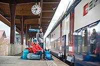 A couple waits on a train station platform in Switzerland with all their ski gear and bags as they begin to travel to Kyrgyzstan for a ski trip.