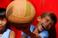 Brazil, Dourados, close-up of boy holding volley ball and laughing with eyes closed Few years ago photographers Anthony Asael and Stepahnie Rabemiafara dreamed a dream that seemed quite imposible: to visit every country of the World promoting arts and tolerance among children and, of course, taking photographs of them. With little money and resources but an impressing will, the duo got an astonishing goal. In four years they visited 300 schools in 192 countries where kids participating of the project created 18,000 pieces of artwork. <br />