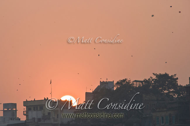 Kite flying is extremely popular.  In this one small area, many kites can be seen against the orange sky. On this afternoon there were thousands of kites flying over Varanasi.<br /> (Photo by Matt Considine - Images of Asia Collection)