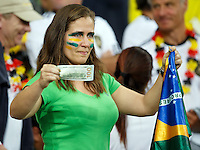 Dejected Brazil fan hold the national flag and a 100 R$ bill