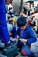 Guatemala, mercato di Chichicastenango. Bambino lustrascarpe.<br /> Guatemala, Chichicastenango market. Shoe-shine boy.