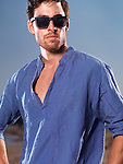 Fashion portrait of a young man in blue shirt and sunglasses at the beach
