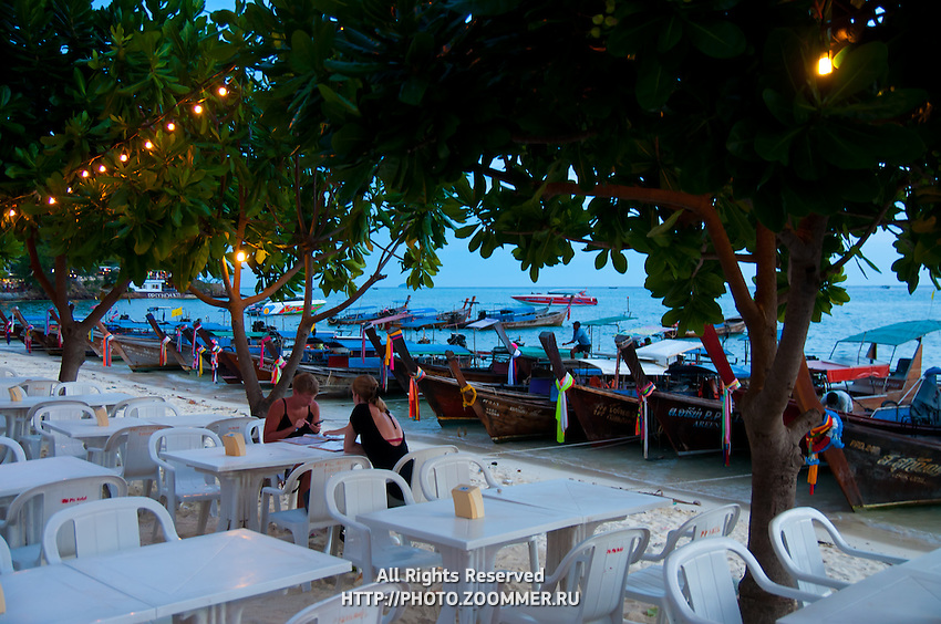 Empty restaurant tables in the port of Phi-Phi island in the sunset, Thailand