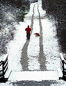 Snow walkers:  A man and his dog decided to make the best of a spring snow fall by taking a walk down a long abandoned railroad track that now serves as community hiking trail.