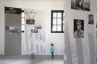 Germany. Bayern state. The Dachau Concentration Camp Memorial Site. A family ( mother and child) stands in the maintenance building which is today the site of the exhibition with pictures of the daily life in the camp. Texts, pictures and photography on the jewish prisoners and the murder of the european jews. On march 22, 1933, the first concentration camp was opened in Dachau by the Nazis. It became a model for all later concentration camps established under the control of the SS men and the Third  Reich. © 2007 Didier Ruef