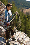 A young woman coils a rope while rock climbing in Grand Teton National Park, Jackson Hole, Wyoming.