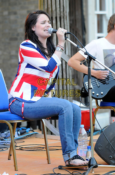 "SCARLETT WILDE .At ""Lawnfest"", an open air concert, West Heath School, Sevenoaks, Kent, England..June 25th, 2009.full length stage concert live gig jeans denim performance music sitting guitar red white blue union jacket cardigan singing .CAP/FIN.©Steve Finn/Capital Pictures."