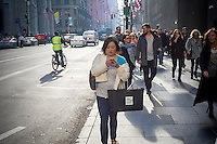 A shopper texts while walking in Midtown Manhattan in New York on Sunday, December 13, 2015. The streets of New York are filled with shoppers and tourists with less than two weeks to Christmas. (© Richard B. Levine)