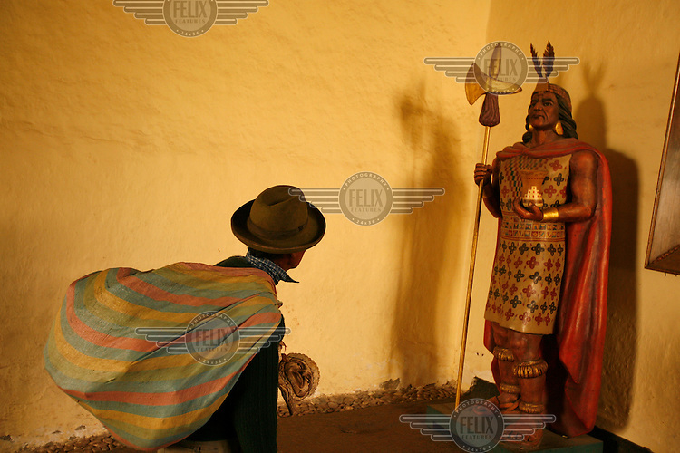 A man selling masks to tourists looks up at a statue of an Inca warrior. Inca culture has become a major attraction bringing tourists to the region.
