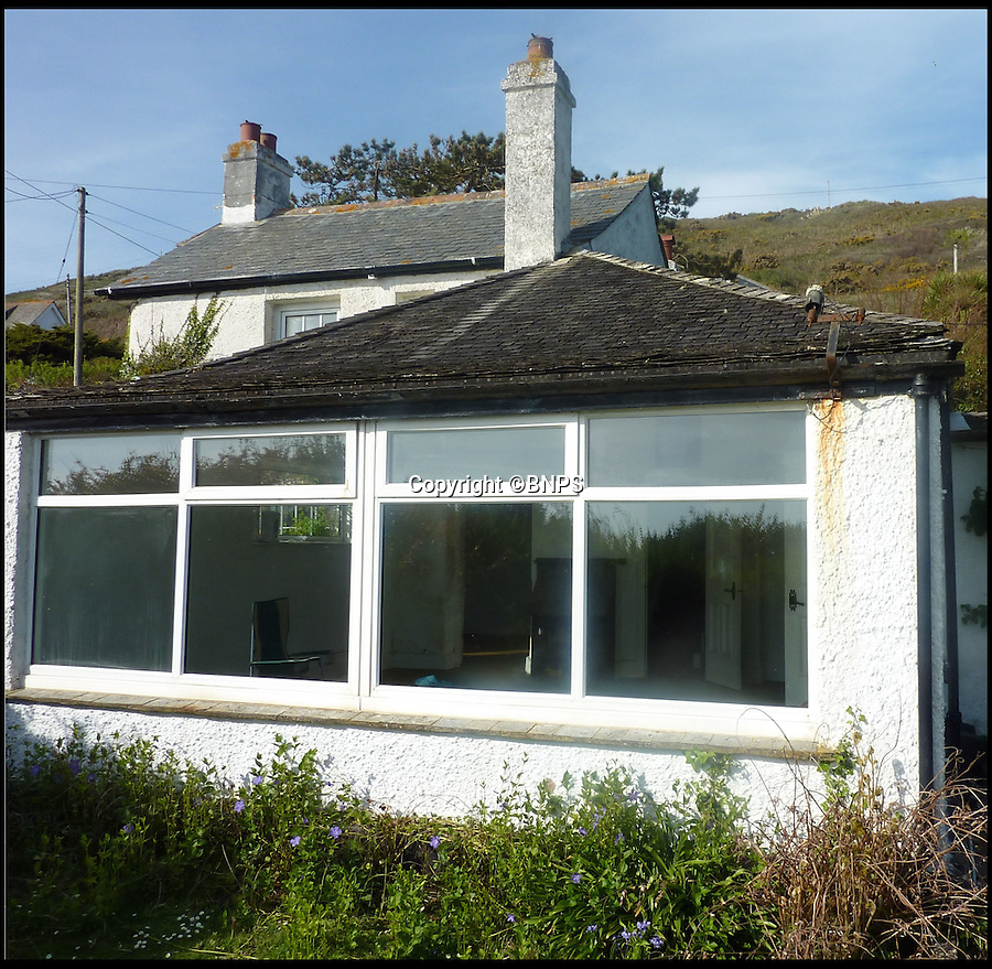 BNPS.co.uk (01202 558833)<br /> Pic: ForeverCornwall/BNPS<br /> <br /> ****Must use full byline****<br /> <br /> The dilapidated cottage when it was concealed by undergrowth.<br /> <br /> When a couple paid out £500,000 for a tumbledown cottage that was fit for nothing but demolition, a few eyebrows were raised among their friends.<br /> <br /> But Alex Michaelis and Susanna Bell's gamble to buy the cliff-top property that had no central heating or electricity has paid off after they turned it into a stunning holiday home now worth three times the purchase price.<br /> <br /> Architect Alex made the most of the stunning views enjoyed from the plot and has ensured all main rooms of the new house, including the four bedrooms and five bathrooms, face the sea.<br /> <br /> They now rent out the modern seaside home overlooking Praa Sands, near Penzance, Cornwall for as much as £5,000 a week.
