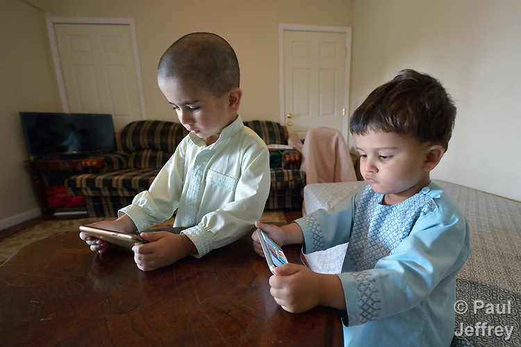 Nasratullah Ahmadzai, 4, and his brother Sanaullah, 2, play games on phones in their home in Harrisonburg, Virginia. Refugees from Afghanistan, they were resettled in Harrisonburg by Church World Service.<br /> <br /> Photo by Paul Jeffrey for Church World Service.