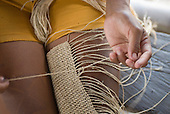 Pará State, Brazil. Aldeia Apyterewa (Parakana). Making a knotted shoulder bag.