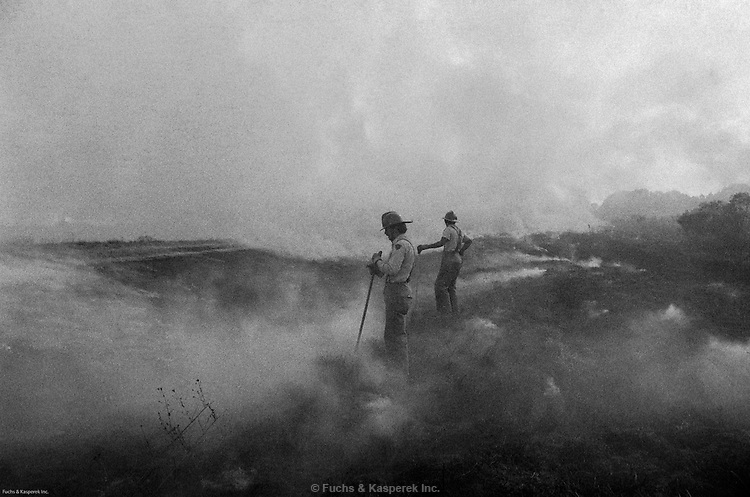 Two firemen pause while battling a brush fire near Jackson, Miss, 1976.