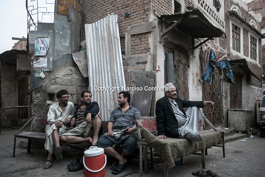 Monday 13 July, 2015: Residents sit at the dusk at one street in the Old City of Sana'a, a 2,500-year-old cultural heritage site endangered after a fighter jet of the Saudi-led coalition bombed and destroyed a line of residential tower-houses killing 4 residents and reducing to rubble the historial site. The ongoing aerial campaign of bombardments by the Arab states and their western allies led by Saudi Arabia and the heavy fighting against the entrenchment of the Houthi insurgency along the Yemeni main cities from north to south has caused an international alert for the enlisted cultural heritage sites in Yemen, such as the historic town of Zabid, the Old City of Sana'a and the Old Walled City of Shibam. (Photo/Narciso Contreras)