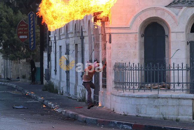 A Palestinian protester throws a molotov cocktail towards Israeli security forces during clashes in the West Bank town of Bethlehem on October 9, 2015. Tension and protests rose after an Israeli man on 09 October stabbed four Palestinians in southern Israel, in what is being seen as a revenge attack, officials said. On 08 October several violent incidents happened, including stabbings which left eight Israelis injured, one Palestinian was killed in East Jerusalem and six in the Gaza Strip in clashes with the army while at least six were injured on the West Bank. Photo by Muhesen Amren