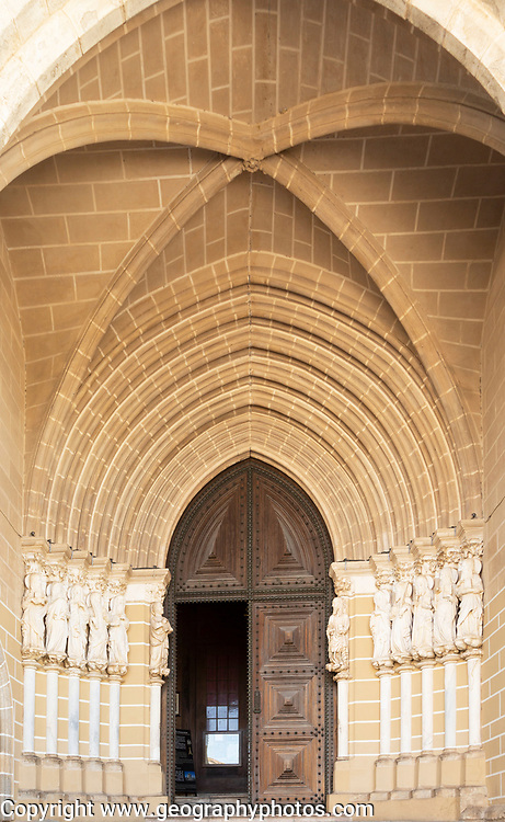 Historic Roman Catholic cathedral church of Évora, Sé de Évora, in the city centre, Basilica Cathedral of Our Lady of Assumption. This image shows details of the carved Gothic period main doorway entrance with carved Apostles either side of the door. The arched ogive or ogival arch is considered a masterpiece of Portuguese Gothic art.