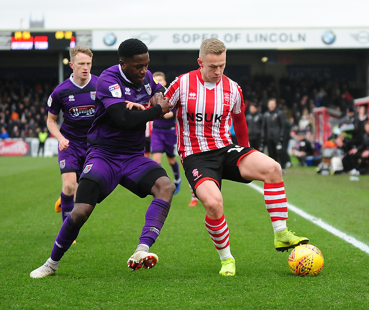 Lincoln City's Danny Rowe shields the ball from Grimsby Town's Mitch Rose<br /> <br /> Photographer Andrew Vaughan/CameraSport<br /> <br /> The EFL Sky Bet League Two - Lincoln City v Grimsby Town - Saturday 19 January 2019 - Sincil Bank - Lincoln<br /> <br /> World Copyright &copy; 2019 CameraSport. All rights reserved. 43 Linden Ave. Countesthorpe. Leicester. England. LE8 5PG - Tel: +44 (0) 116 277 4147 - admin@camerasport.com - www.camerasport.com