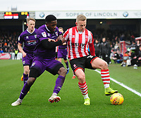 Lincoln City's Danny Rowe shields the ball from Grimsby Town's Mitch Rose<br /> <br /> Photographer Andrew Vaughan/CameraSport<br /> <br /> The EFL Sky Bet League Two - Lincoln City v Grimsby Town - Saturday 19 January 2019 - Sincil Bank - Lincoln<br /> <br /> World Copyright © 2019 CameraSport. All rights reserved. 43 Linden Ave. Countesthorpe. Leicester. England. LE8 5PG - Tel: +44 (0) 116 277 4147 - admin@camerasport.com - www.camerasport.com