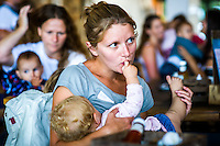 Mothers who have come together to celebrate the annual Big Latch On breastfeeding promotion event breastfeeding in a cafe. The baby puts its finger in the mum's mouth while feeding.