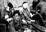 Men of the American assault troops of the 16th Infantry Regiment, injured while storming a coastal area code-named Omaha Beach during the Allied invasion of the Normandy, wait by the chalk cliffs at Collville-sur-Mer for evacuation to a field hospital for further treatment, June 6, 1944.  (AP Photo)