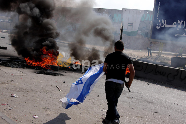 A Palestinian protester prepares to burn an Israeli flag during clashes at the Kalandia checkpoint near the West Bank city of Ramallah October 9, 2009. Palestinian leaders on Thursday called for a one-day general strike and warned of more street protests over Jerusalem, where clashes at the flashpoint al-Aqsa mosque two weeks ago cranked up tensions in the disputed city. Israel is playing down Palestinian warnings that its security tactics risk a new Palestinian uprising. Photo by Issam Rimawi