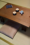 Japanese short-legged wooden tea table, Chabudai, with a teapot and two cups, sitting cushions, Zabuton, on tatami mats of a traditional Japanese room in a Ryokan inn in Kyoto, Japan
