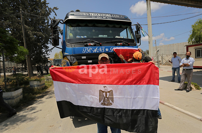 A Palestinian man holds an Egyptian flag in front of Egyptian truck carrying fuel after entering the southern Gaza Strip from Egypt through the Rafah border crossing on June 21, 2017. Egypt began to deliver a million litres of fuel to Gaza, a Palestinian official said, in an attempt to ease the Palestinian enclave's desperate electricity crisis. The fuel, trucked in through the Rafah border between Egypt and Gaza, will be routed to the territory's only power station -- closed since April due to fuel shortages. Photo by Ashraf Amra
