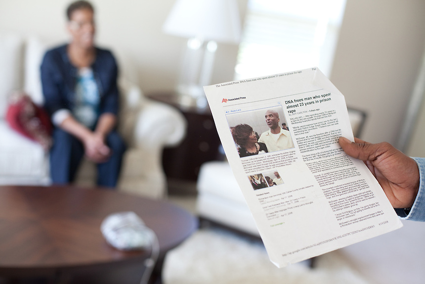 Thomas McGowan holds a copy of a news article written about his release from prison. HIs girlfriend Kim Moses sits in the background inside McGowan's home in Garland, Texas.