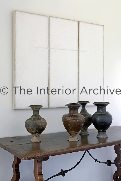 A monochrome triptych by Renaart Evens hangs above an 18th century Spanish console table with its collection of 13th century terracotta Khmer vases