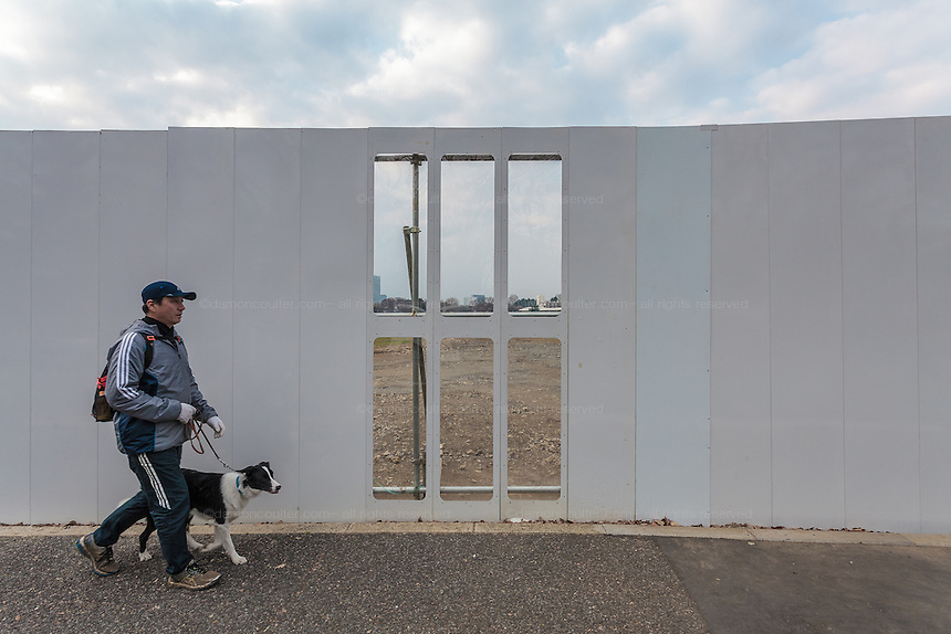 A man walks his dog by the wall shielding  the construction site of the new Olympic Stadium in Tokyo, Japan. Friday March 4th 2016 The site of the old old national Stadium has been cleared in readiness for the new Olympic stadium designed by British/Iraqi architect , Zaha Hadid. The designs was modified and then cancelled when expected costs skyrocketed and a new stadium design has yet to be finalised.