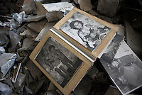 Old family portraits found in a house destroyed by shelling. Snizhne, Ukraine.