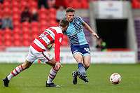 Danny Rowe of Wycombe Wanderers plays the ball under pressure from Matty Blair of Doncaster Rovers during the Sky Bet League 2 match between Doncaster Rovers and Wycombe Wanderers at the Keepmoat Stadium, Doncaster, England on 29 October 2016. Photo by David Horn.