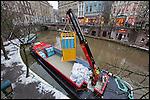 Nederland, Utrecht, 15-01-2010 Het eerste elektrisch aangedreven vrachtschip van Nederland werd vandaag gedoopt  in de Oudegracht. De zogenaamde bierboot gaat de horeca in de binnenstad van drankvoorraad voorzien. Utrecht kent sinds 1996 een bierboot met dieselmotor, als vervanger van vrachtwagens die moeilijk kunnen manoeuvreren in de middeleeuwse binnenstad. De tweede bierboot (18,80 meter) vaart geheel elektrisch en is CO2-neutraal. Ook de kraan waarmee de fusten en kratten worden overgeheveld, werkt op elektriciteit.De nieuwe bierboot is mede gefinancierd uit het Actieplan Luchtkwaliteit, het project wordt gesubsidieerd door de Europese Unie. FOTO: Gerard Til / Hollandse Hoogte...