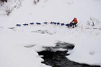 Billy Snodgrass runs along the shelf ice near open water in the Dalzell Gorge on the trail between Rainy Pass summit and Rohn, Interior Alaska, 2010 Iditarod