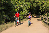 Young couple on mountain bikes, exploring the trails of Zilker Park Hike And Bike Trail in Austin, Texas.