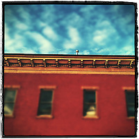 iPhone photo of Westerville Antiques building roofline with blue skyand clouds.