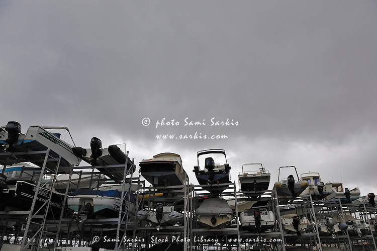 Motor Boats on racks at harbor by stormy sky