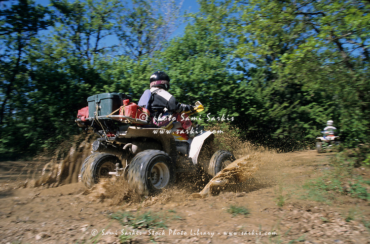 Person on a quadbike travelling over muddy terrain, Luberon, Provence, France.